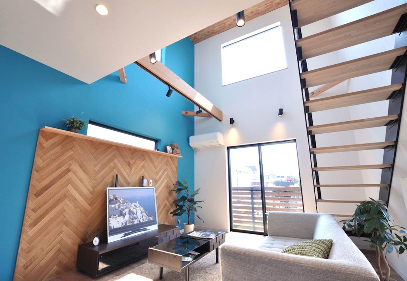 Asobi-創家(アソビスミカ)/ナカジツ【デザイン住宅、趣味、間取り】リビングは高い吹抜けを採用したことで、床面積31坪とは思えないほどの開放感がある。窓も大きめに取り、十分な光と風を採り込める。ビビッドなブルーのクロスに無垢のヘリンボーン貼りが絶妙にマッチし、海辺のリゾートホテルのような雰囲気を演出