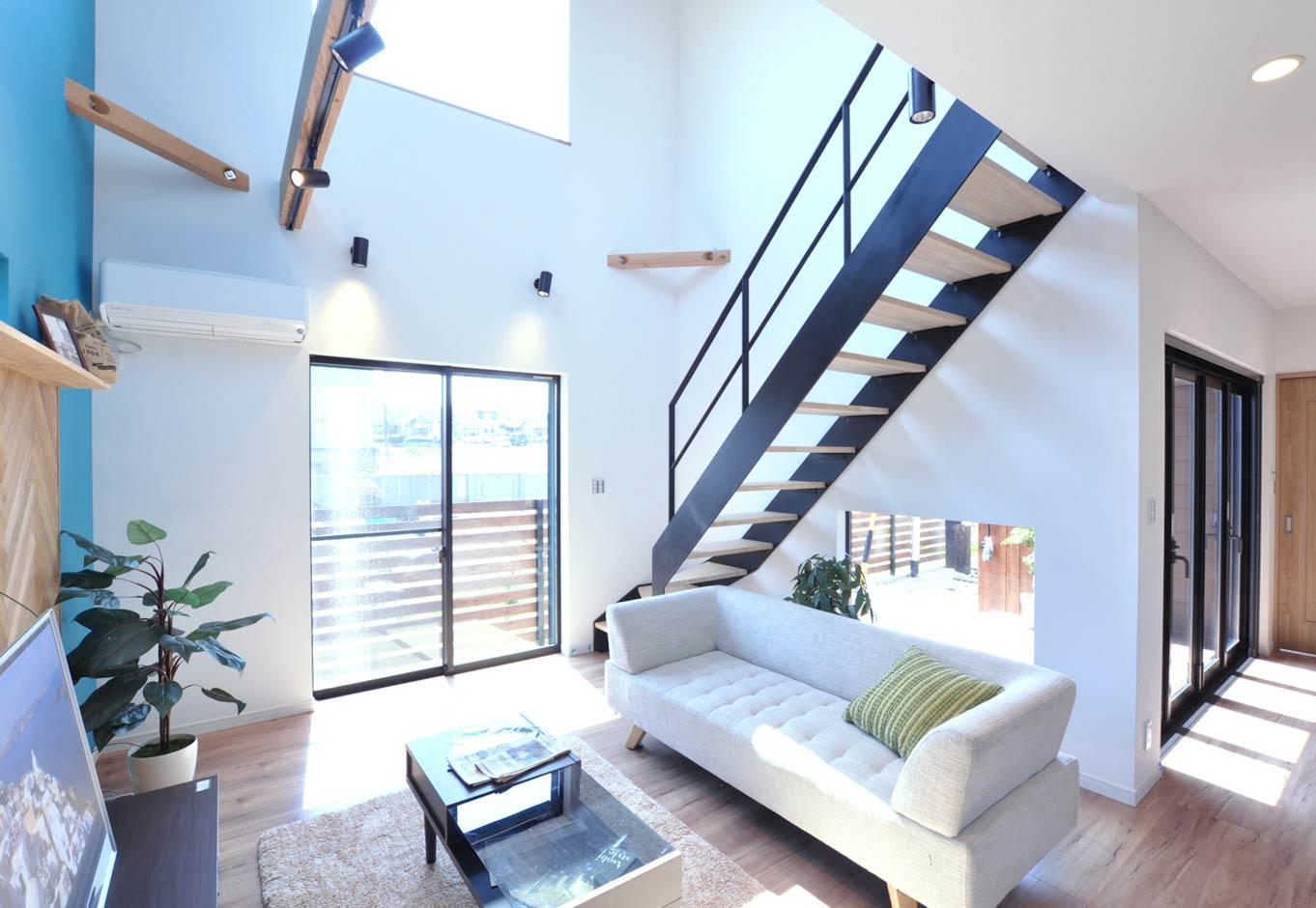 黒い鉄骨階段が白を基調とした空間のアクセントに。スケルトンにしたことでより開放感を創出。階段下のFIX窓越しにはウッドデッキが見える。床を無垢調の合板フローリングにしてコストを抑えた