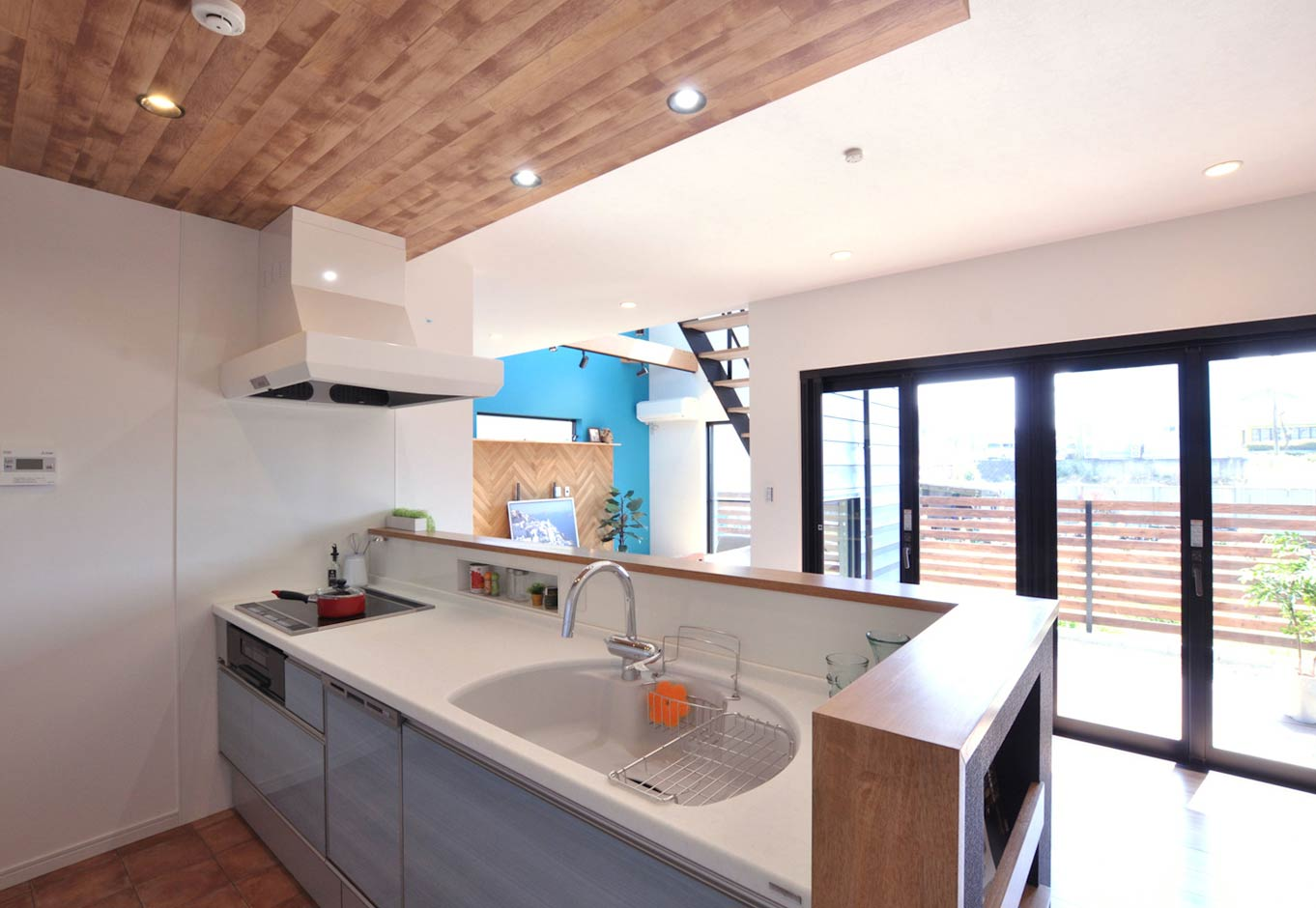 Asobi-創家(アソビスミカ)/ナカジツ【デザイン住宅、趣味、間取り】LDKとウッドデッキをつなぐ窓は、折れ戸式のフルオープンサッシを採用。キッチンから遠くまで目線が抜けて開放感抜群。天井は木目調のクロス