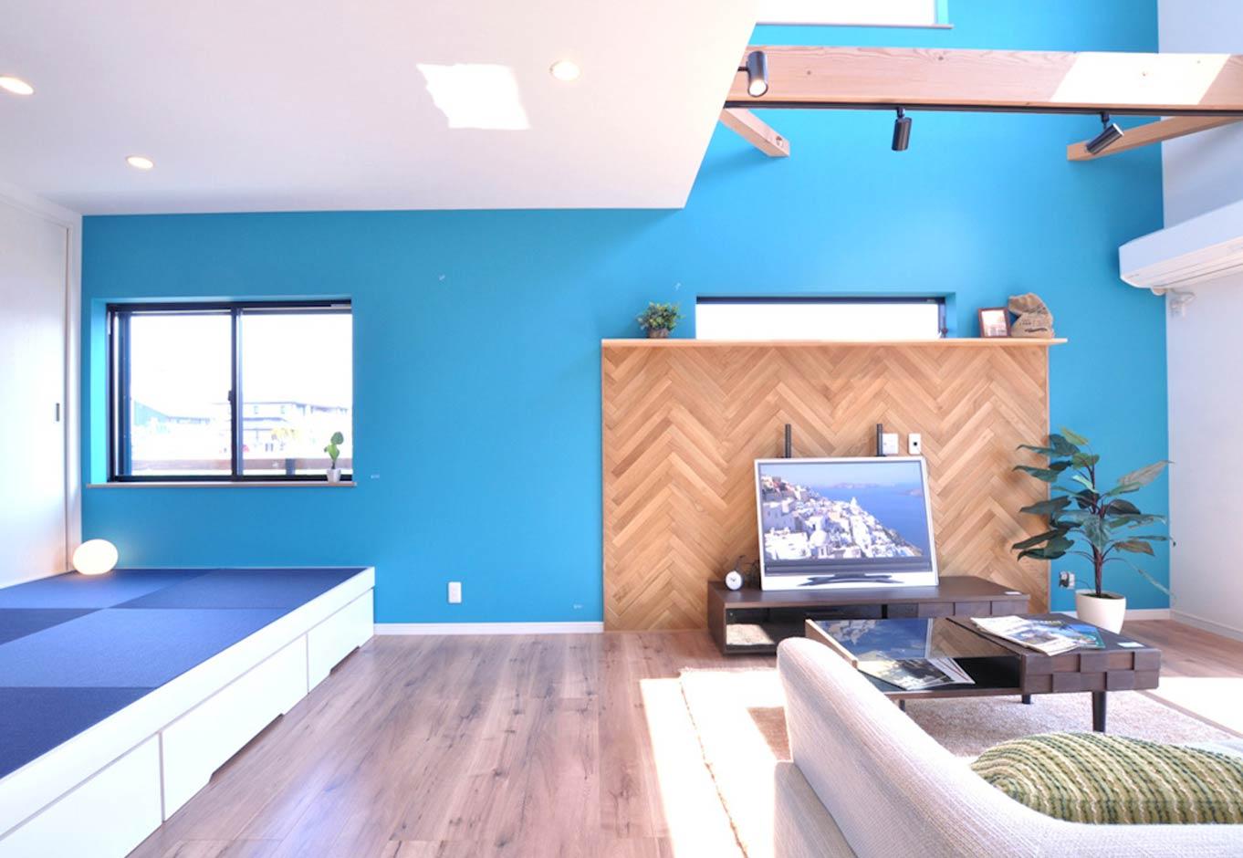 Asobi-創家(アソビスミカ)/ナカジツ【デザイン住宅、趣味、間取り】リビングと隣接する小上がりの畳コーナー。青い市松模様の畳の下は収納スペース。客間として使うのはもちろん、洗濯物をたたんだり、赤ちゃんをお昼寝させる場所として重宝している。ベンチ代わりに腰かけると、ソファと目線の高さが同じになり、コミュニケーションを取りやすい