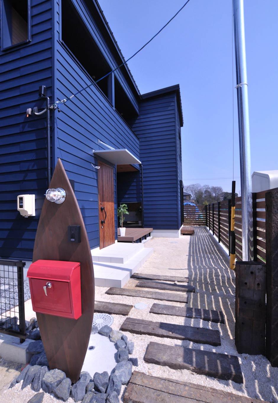Asobi-創家(アソビスミカ)/ナカジツ【デザイン住宅、趣味、間取り】アメリカ西海岸を彷彿とさせるアプローチ。海をイメージした濃いブルーの外壁が太陽光に美しくきらめく。サーフボードをモチーフにした造作のオブジェにも趣がある