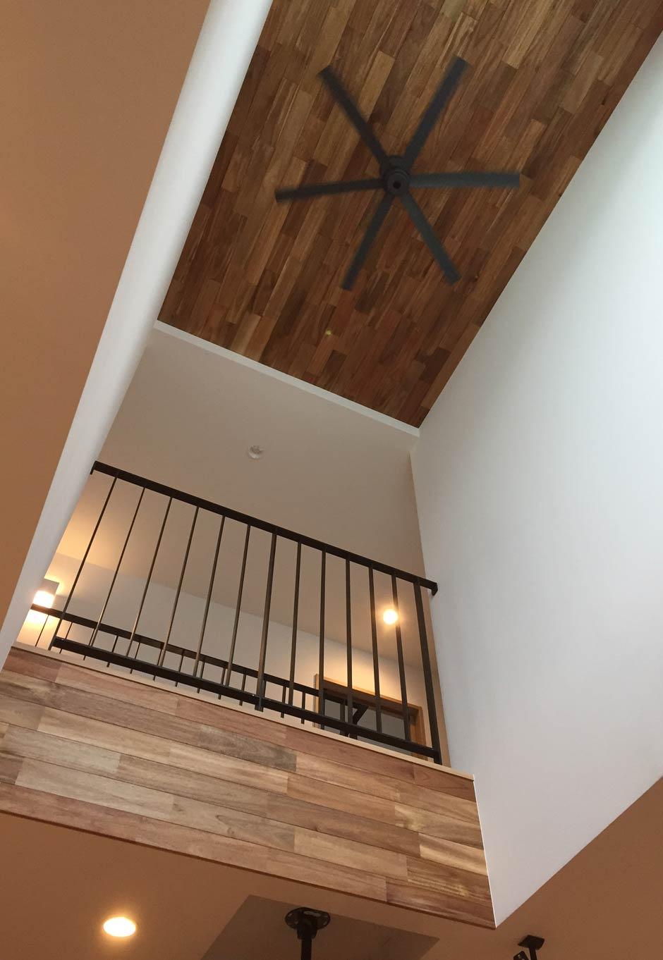 Asobi-創家(アソビスミカ)/ナカジツ【趣味、省エネ、間取り】吹抜けの天井、垂れ壁もすべて無垢材にこだわり、高級感を演出。アイアンの手すりがナチュラルな空間を引き締めている