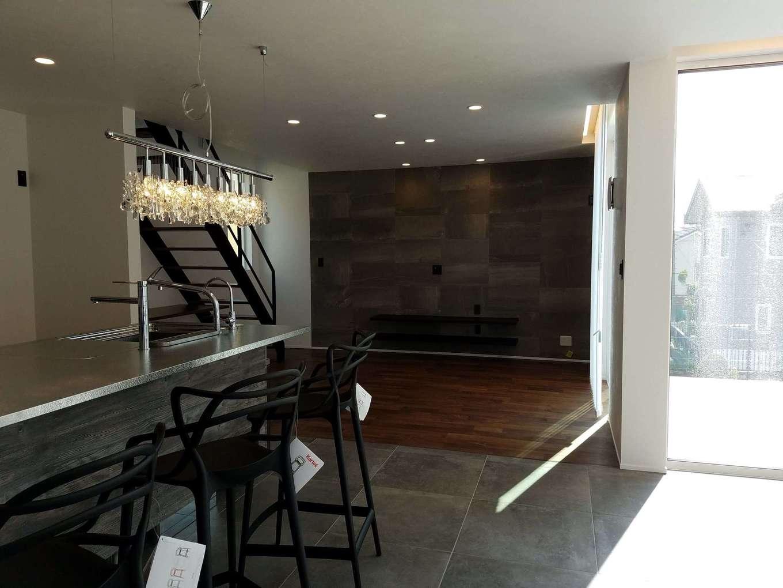 Asobi-創家(アソビスミカ)/ナカジツ【デザイン住宅、高級住宅、間取り】モノトーンを基調とした29畳のLDK。リビングの床だけ無垢材を使い、その他はすべてタイルで統一した。テレビステーションのアクセントウォールが無機質な空間で存在感を放っている
