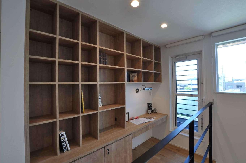 壁一面に作った大容量の書棚はファミリーライブラリーとして活用。一角にカウンターデスクも造作した。そのまま広いバルコニーへと出られる