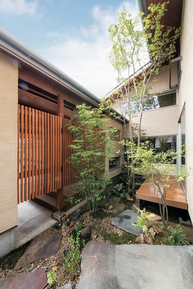 屋根上まで伸びる高木と、石、下草が豊かさと風情を感じさせる