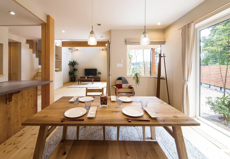 庭の景色を眺めながら食卓を囲むダイニング。南面の大きな開口部に加え、構造計算に基づき、通常の住宅では難しい位置にFIXの窓を設けたことで、視線が遠くまで抜ける