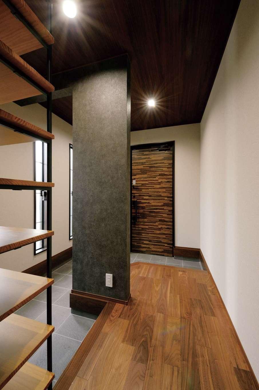 朝日住宅【デザイン住宅、自然素材、間取り】ドアと廊下の木目が映える玄関ホール。木とアイアンで造ったオリジナルの靴入れがおしゃれ