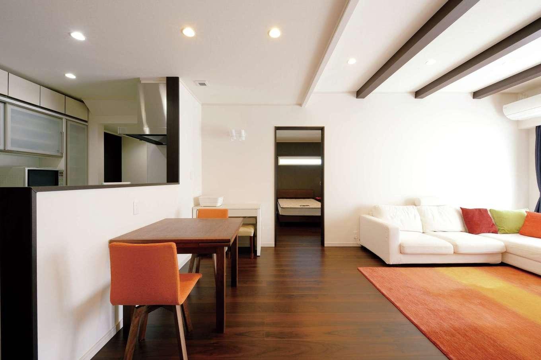 """朝日住宅【デザイン住宅、省エネ、平屋】対面式キッチンからリビングを見渡せる造り。ダイニングテーブルの隣にメイクデスクを用意するなど、""""リビングで生活が完結する""""よう配慮した。キッチンの奥には、奥さまがこもるための3畳程度の書斎を用意"""