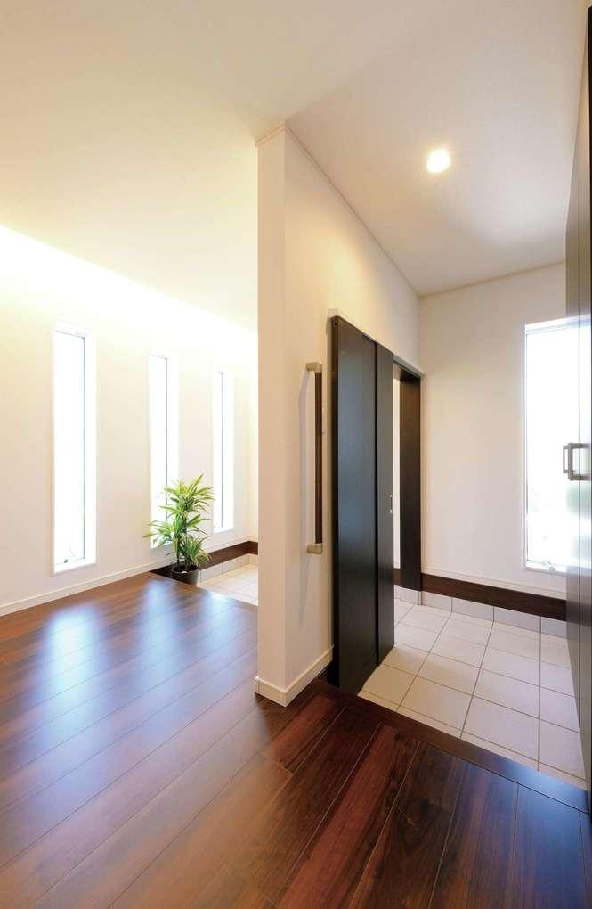 朝日住宅【デザイン住宅、ペット、ガレージ】左側は来客用の玄関ホール、右側はガレージに繋がる家族用の玄関。プライバシーを保ちながら開放感があり、収納スペースもたっぷり確保してある