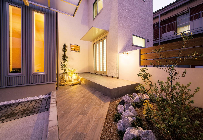 朝日住宅【デザイン住宅、子育て、自然素材】コの字型の建物の奥に設けられたネイルサロンの入口。アプローチには木目調のタイルを貼りリゾートチックに演出
