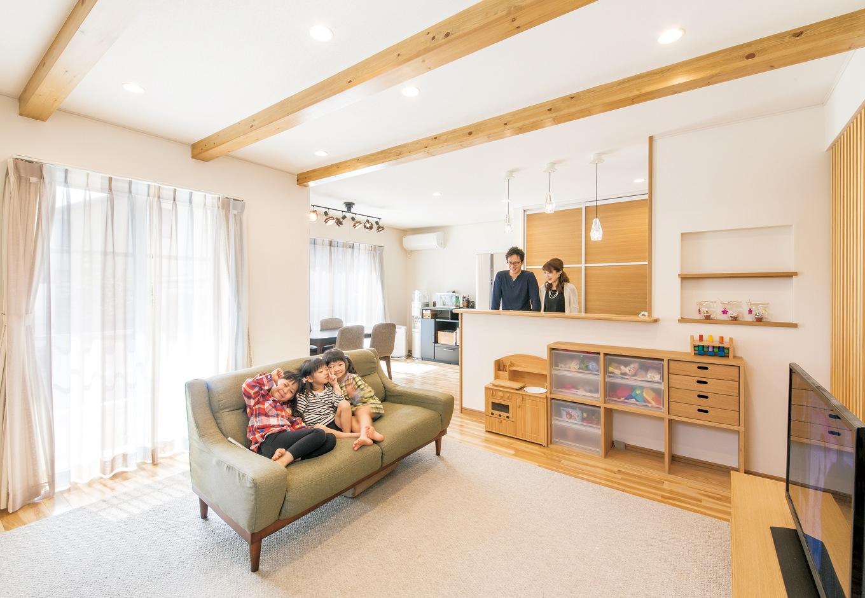 朝日住宅【デザイン住宅、子育て、自然素材】南面に開口部を大きくとり、明るさと開放感を確保したLDK。照明はポイント となる箇所以外はダウンライトで統一 し、天井の梁を際立たせてシンプル&ナチュラルな空間を演出。床のサクラ材のやさしい木目が奥さ まのお気に入り