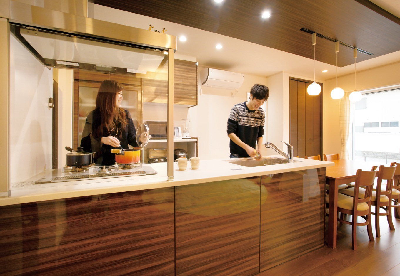 朝日住宅【デザイン住宅、二世帯住宅、間取り】レストランを思わせるスタイリッシュなキッチンは、両親も使いやすいようガスを選んだ。調理台の前にガラスで仕切りを入れ、家族の顔が見えるよう配慮