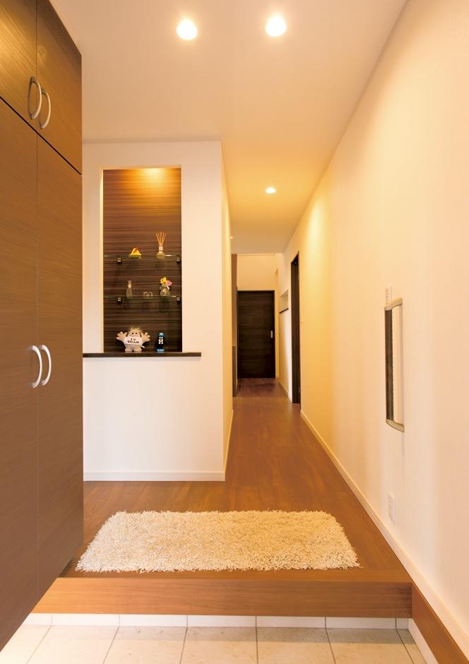 朝日住宅【デザイン住宅、二世帯住宅、間取り】飾り棚や間接照明がシックな印象の玄関ホール。向かって左側には両親用の和室、右手奥にはLDKへ続くドアがある