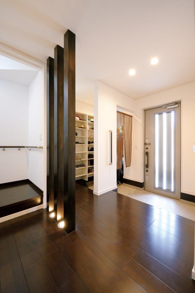 朝日住宅【デザイン住宅、収納力、間取り】家族用と来客用を分けた玄関ホールは、収納もたっぷりで使い勝手抜群。格子の足元に光る照明がアクセント