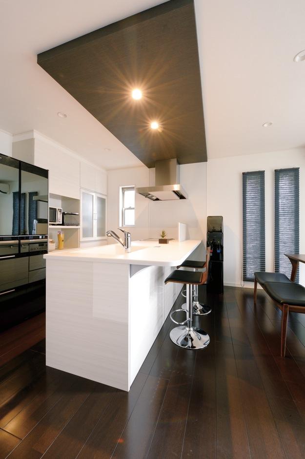 朝日住宅【デザイン住宅、収納力、間取り】幅259cmとゆとりある対面式キッチンは、床や天井とのコントラストがお洒落。カウンター席も用意され、軽い食事やお酒を楽しむのにぴったりだ