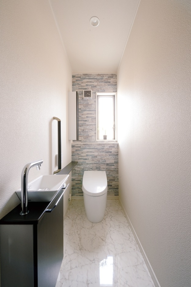 朝日住宅【デザイン住宅、収納力、間取り】壁紙の一部に石積み調クロスを使い、トイレまでシックに