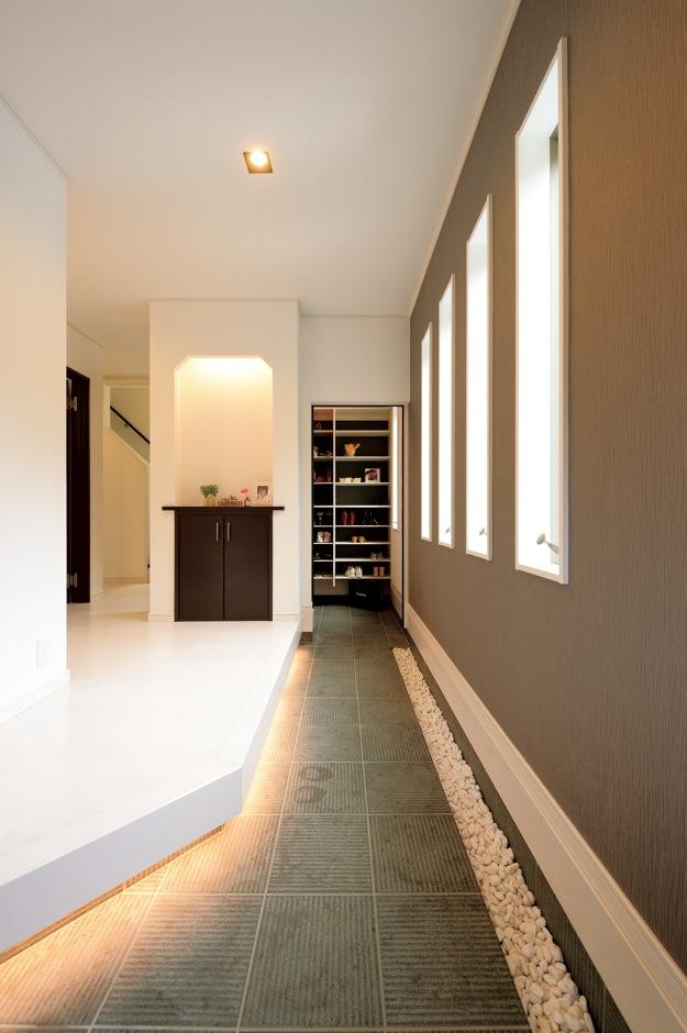 朝日住宅【デザイン住宅、間取り、インテリア】奥に扉付きの収納スペース兼家族用玄関があるため、土間部分は余計な物がなくきちんとした印象。等間隔で並ぶ小窓や、壁際に敷いた玉砂利もアクセントに