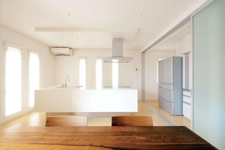 朝日住宅【デザイン住宅、収納力、省エネ】奥さまが展示場で一目惚れした、深澤直人氏デザインのアイランド式キッチンを採用。隣には扉付きパントリーがあり、冷蔵庫の奥にも収納スペースを用意