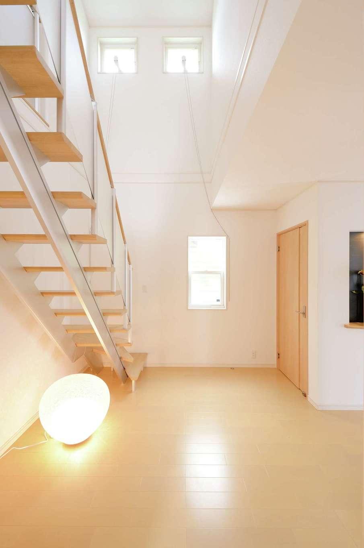 朝日住宅【デザイン住宅、収納力、省エネ】玄関を入ると、この吹き抜けの階段ホールが迎えてくれる。自然光が優しく反射し、いつも明るい印象