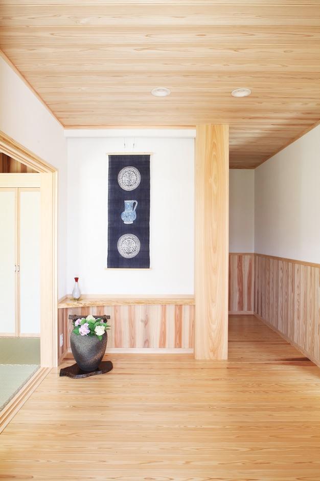 広々とした玄関で家族やゲストを出迎えるのは35cm角のヒノキの大黒柱。正面の壁は腰板を低くして白壁の面積を広くとり、タペストリーや絵画を飾れるようにした