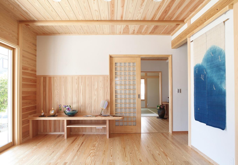 造作の飾り棚を壁面に配したリビング。床・腰壁・天井は無節の天竜杉、壁は珪藻土。藍染めのタペストリーが白壁に映える