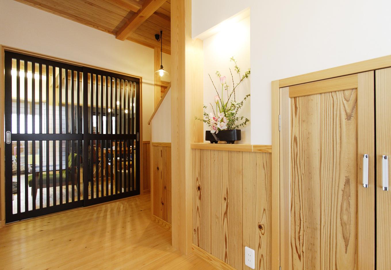 村木建築工房【収納力、和風】玄関ホールとLDKの仕切り戸には、古民家風の格子の引き戸を使用。板倉造りの空間のアクセントとして室内全体を引き立てている