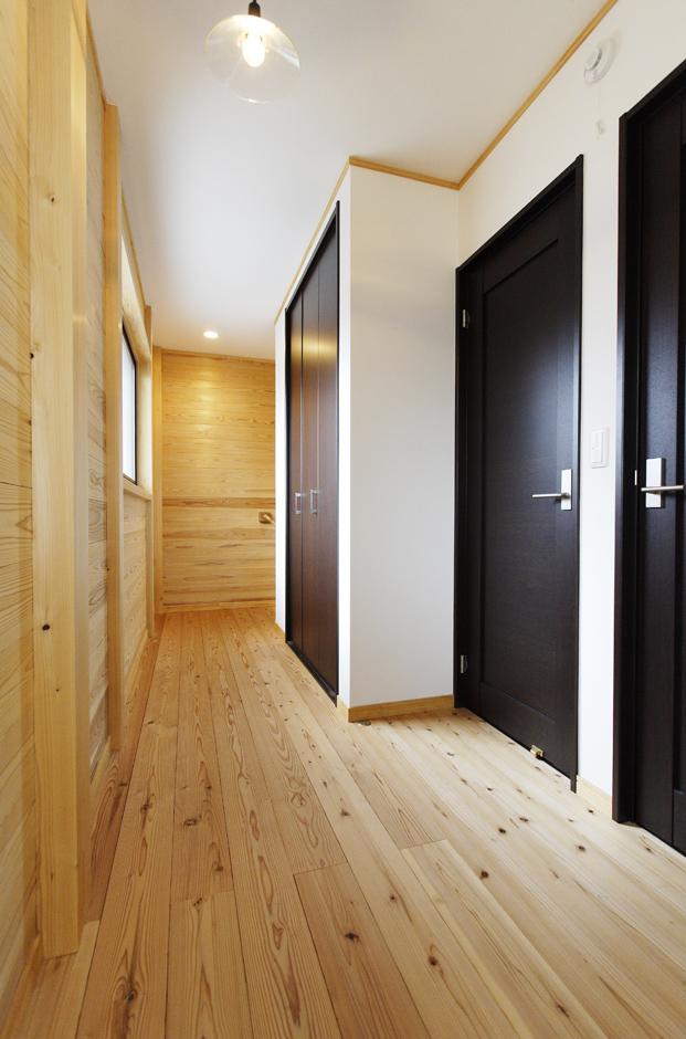 村木建築工房【収納力、和風】2階は1階とは雰囲気を変えて、シンプルモダンなテイストを強調。ぬくもり豊かな板張りの床・壁と、無機質な黒いドアとの対比が面白味を感じさせる