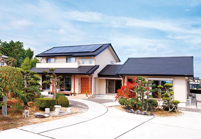 平屋建てと2階建てから成る完全分離型の2世帯住宅。外観は切妻屋根の横のラインを強調