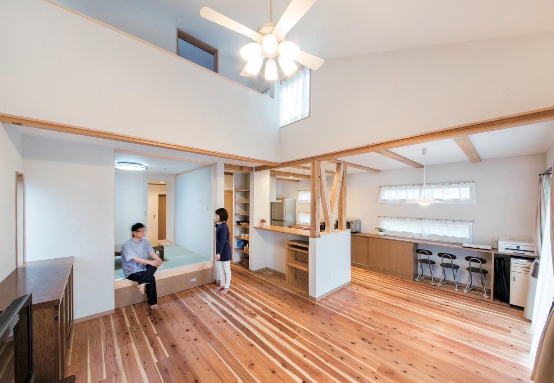 水田建設【デザイン住宅、自然素材、省エネ】天竜杉の床とシラス壁が心地よいLDK。リビングの吹抜けや、キッチンの仕切りの筋交いが「抜け感」を強調し、 実際以上の広さを感じさせる