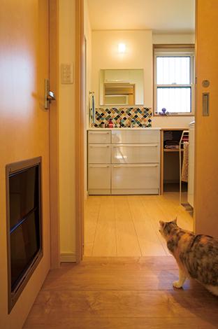 水田建設【自然素材、間取り、ペット】トイレのドアに「ねこ穴」を開け、自由に行き来できるようにした。洗面のカラフルなモザイクタイルは奥さまのこだわり