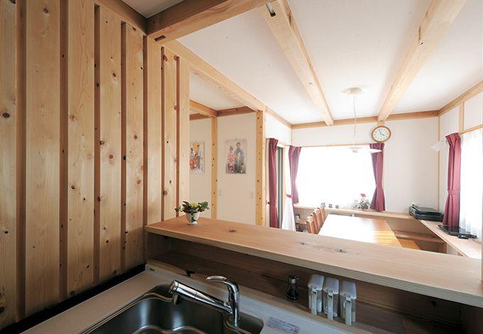 水田建設【子育て、収納力、自然素材】便利な調味料入れを造作したキッチン。表面のキッチンパネルも木の収納庫になっている。杉板の格子でさりげなく目隠しも