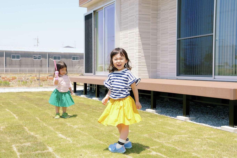 幹工務店【デザイン住宅、子育て、自然素材】LDKに面する広い庭は、子どもたちの安全な遊び場。キッチンは窓に向いた対面レイアウトで、窓の外が見渡しやすいよう配置している