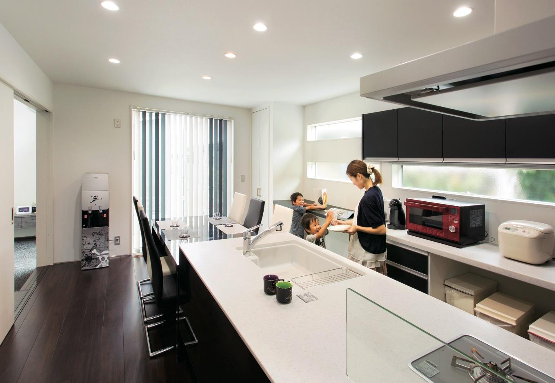 幹工務店【デザイン住宅、省エネ、間取り】アイランドキッチンは共働きのご夫妻が協力し合って作業できる大きなワークトップが特徴。随所に窓を効果的に設け、明るく清々しい空間を実現