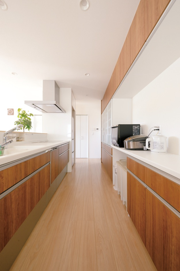 幹工務店【子育て、収納力、省エネ】回遊性の高いアイランドキッチン。サニタリーへ一直線につながる動線も便利。冷蔵庫を隠し、なるべく生活感を出さないようにしている