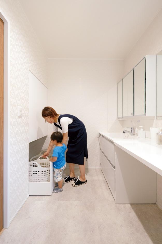 幹工務店【子育て、収納力、省エネ】家族全員が入っても混雑しない脱衣所。洗剤などをしまう棚、脱いだ服を入れるスラ イド収納を造作。洗面台横のカウンターは子どもの髪をカットしたりできて便利