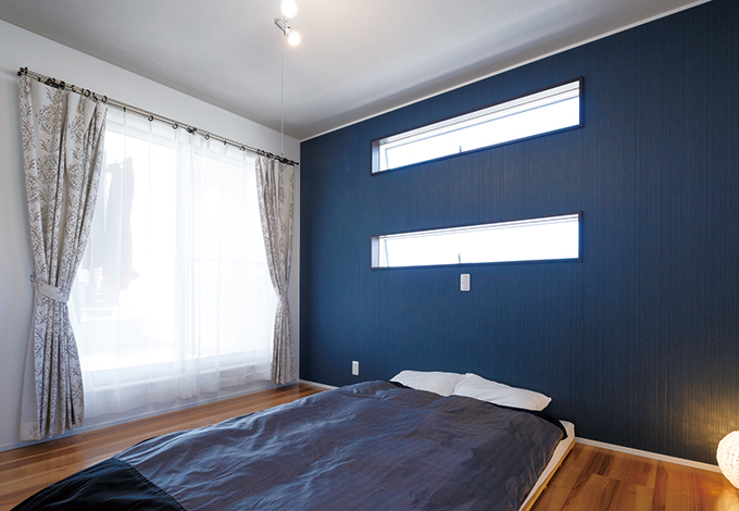 幹工務店【子育て、収納力、間取り】主寝室のダークなクロスはご主人のお気に入り。窓を開ければ屋根付きのバルコニーへ。3畳のウォークインクローゼットも完備