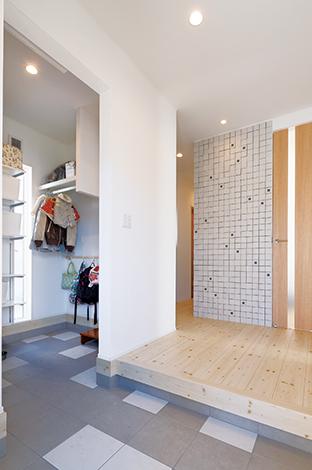 幹工務店【子育て、収納力、間取り】ランダムに配置した玄関ホールのタイルと、凹凸のある正面の壁のタイルは奥さまのこだわり。広い土間収納はコートも掛けられて便利