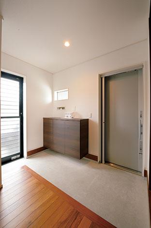 無機質な空間を演出するために、あえてモルタル仕上げにした玄関土間。キッチンの勝手口の代わりに、車庫から濡れずに出入りできるドアを付けた