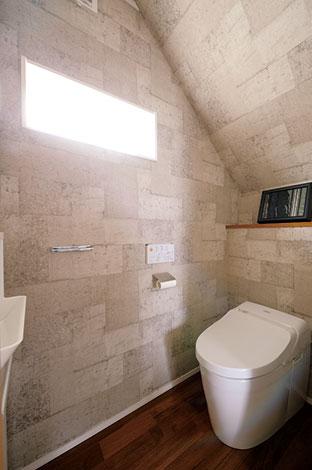 階段下のデッドスペースを利用したトイレ。コンクリート調のクロスで遊び心を演出
