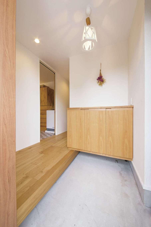 幹工務店【デザイン住宅、子育て、省エネ】モルタルの土間と白壁と木目が調和した玄関。玄関のすぐ先に洗面・浴室があり、帰宅後の手洗いや着替えが便利