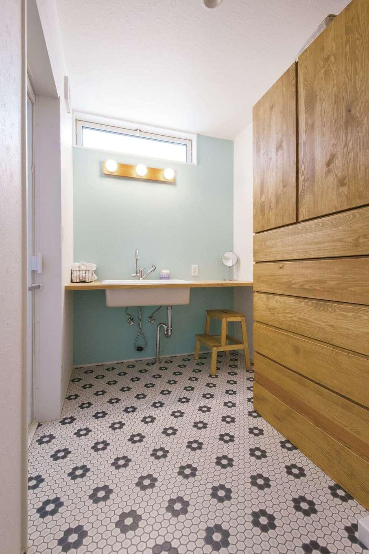 幹工務店【デザイン住宅、子育て、省エネ】ポップな柄のクッションフロアと水色の壁の組み合わせがオシャレな洗面スペース。洗面台はシンプルにデザイン。家族の下着やリネン類をしまえる造作家具も設置