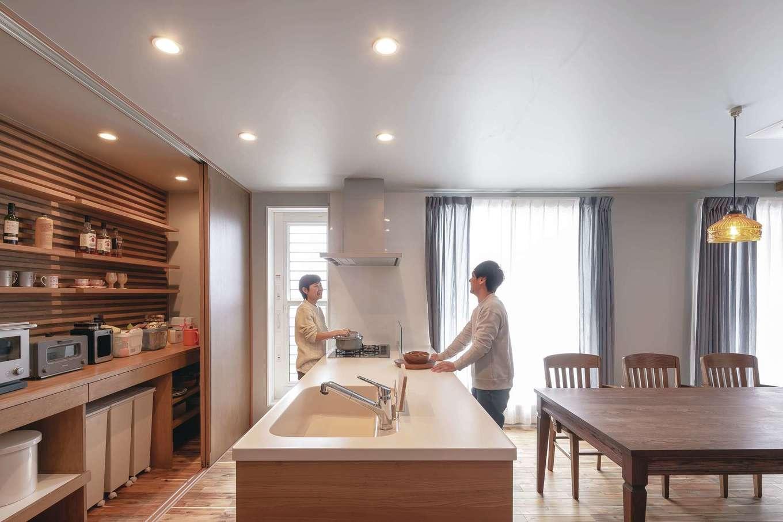 幹工務店【デザイン住宅、自然素材、インテリア】キッチンの背面には大きな扉で電化製品や用品類をすっぽりと「隠す収納」を確保。収納の壁面は棚の高さを変えられる木製パネル仕上げで「見せる収納」も楽しめる