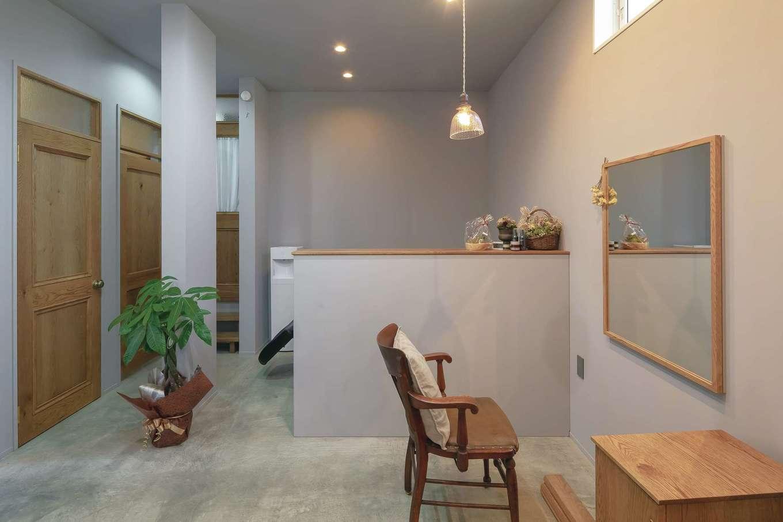 幹工務店【デザイン住宅、自然素材、インテリア】美容サロン内の壁と天井は淡いグレーの塗装でフラットに仕上げてある。ムラの無い美しい仕上がりに職人の技術力の高さが感じられる。カウンターの奥に自宅へ通じる出入口がある