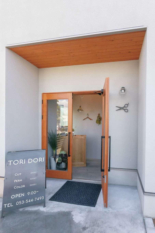 幹工務店【デザイン住宅、自然素材、インテリア】美容サロンのエントランス。板張りの軒や木の扉が塗り壁に映える。地域の人々に何のお店かわかってもらえるように、壁にスチール製のハサミのオブジェを飾った
