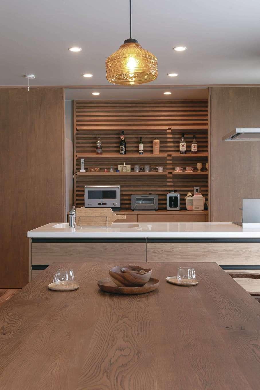 幹工務店【デザイン住宅、自然素材、インテリア】オープンキッチンの収納スペースの壁面の木製パネルはモデルハウスを参考にしたもので、『幹工務店』のオリジナル。照明に木のラインが映え、カフェのようにオシャレな雰囲気