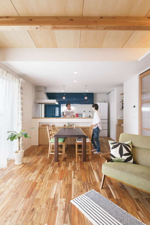 幹工務店【自然素材、間取り、ガレージ】アカシアの無垢の床と塗り壁がおりなすLDKは、木の香りがほのかに漂う心地よい空間。和室との仕切り戸はハイドア仕様の造作建具を採用し、開放感を強調した