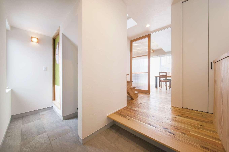 幹工務店【自然素材、間取り、ガレージ】広い土間が広がる玄関。土間はLDKと和室の両方に通じている。モルタル調の土間とアカシアの無垢の床のコントラストもスタイリッシュ