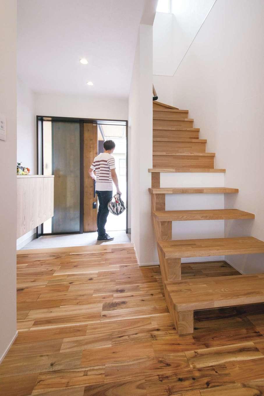 幹工務店【自然素材、間取り、ガレージ】廊下や玄関ホールのスペースにゆとりを持たせ、行き来がしやすい動線を確保。壁際の棚には小物をオシャレにディスプレイ