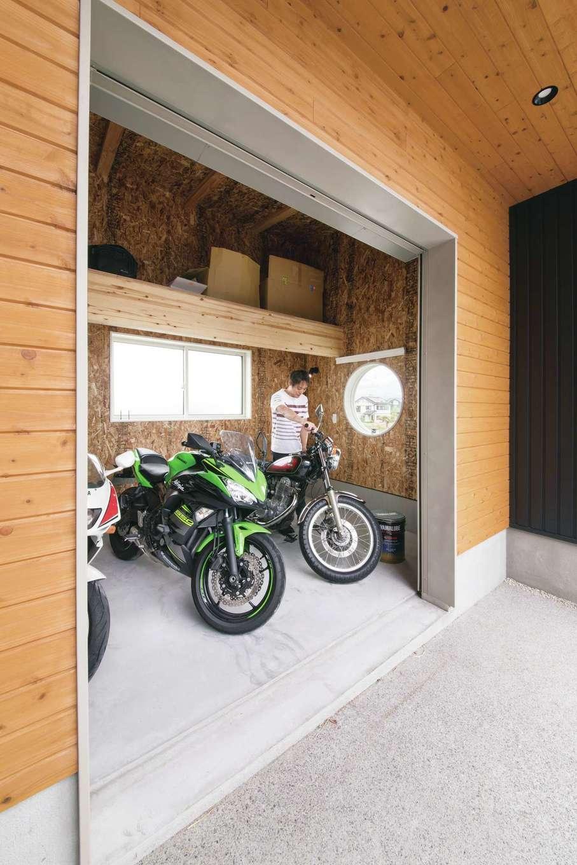 幹工務店【自然素材、間取り、ガレージ】7畳のバイクガレージは、3台分のバイクをゆうに格納できる広さ。道路側に丸窓を設けたのはご主人のこだわり。荷物をしまえる棚も設けてある