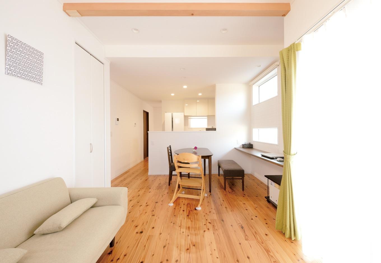 Um House(マル祐戸田建築)【子育て、収納力、間取り】リビングから家事室までゆったりとつながり、どこにいても家族の気配を感じることができる。リビング収納のおかげで、散らかりがちな子どものおもちゃもすっき り。ダイニング横にカウンターを造作。ここだけ壁紙を変え、Mさんも集中して仕事ができる空間になった